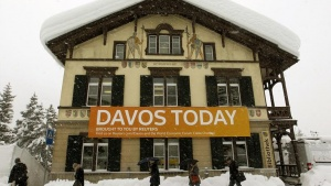 People walk past a banner of Reuters News in front of their office during the World Economic Forum (WEF) at a library in the Swiss mountain resort of Davos January 24, 2012. The upcoming WEF will be held from January 25 to 29.     REUTERS/Arnd Wiegmann (SWITZERLAND - Tags: POLITICS BUSINESS)