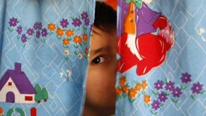 An autistic child peers from between curtains at the Consulting Center for Autism in Amman, March 30, 2010, one of the few places in Jordan that helps children with the condition. REUTERS/Ali Jarekji