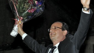 France's newly-elected President Francois Hollande holds a red roses bouquet as he celebrates on stage after results in the second round vote of the 2012 French presidential elections in Tulle May 6, 2012. REUTERS/Jacky Naegelen