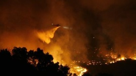 A helicopter drops flame retardant on a brush fire burning in Rancho Palos Verdes, California August 27, 2009. REUTERS/Mario Anzuoni