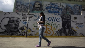 "A woman walks past a mural depicting Libya's former leader Muammar Gaddafi and Mexican rebel Subcomandante Marcos in the low income neighborhood of '23 de Enero' in Caracas August 10, 2012. With a presidential election looming on Oct. 7, opposition members fear the ""colectivos""- radical organizations that call themselves the guardians of Hugo Chavez's socialist project and defenders of their local communities, will turn to violence if challenger Henrique Capriles defies the polls and wins. Picture taken on August 10, 2012. REUTERS/Carlos Garcia Rawlins (VENEZUELA - Tags: POLITICS CIVIL UNREST ELECTIONS)"