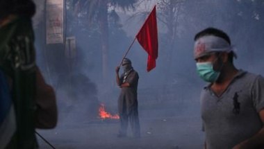 "A protester holds a red flag as he stands amongst teargas smoke during an anti-American protest rally to mark the ""Day of Love"" iin Islamabad September 21, 2012. REUTERS/Akhtar Soomro"