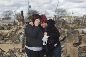 Neighbors embrace after looking through the wreckage of their homes  in the Breezy Point section of Queens. REUTERS/Shannon Stapleton