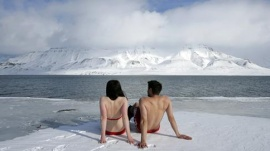 "Climate activists Lesley Butler and Rob Bell ""sunbathe"" on the edge of a frozen fjord in the Norwegian Arctic town of Longyearbyen April 25, 2007. REUTERS/Francois Lenoir"