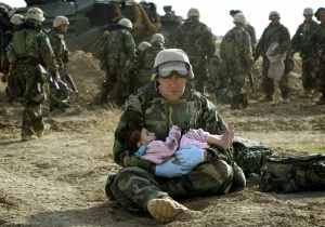 U.S. Navy Hospital Corpsman HM1 Richard Barnett, assigned to the 1st Marine Division, holds an Iraqi child in central Iraq in this March 29, 2003 file photo. REUTERS/Damir Sagolj