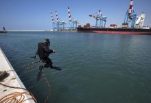 A scuba diver jumps in the water at the port of the northern city of Haifa, April 23, 2013. REUTERS/Ronen Zvulun