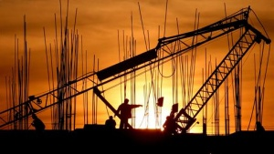 Construction workers work at a site as the sun sets in the northern Indian city of Chandigarh December 16, 2006.  REUTERS/Ajay Verma/Files