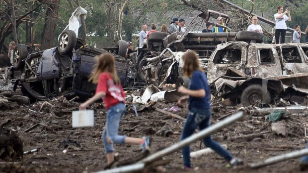 People look through the wreckage of their neighborhood after a tornado struck Moore, Oklahoma, May 20, 2013. REUTERS/Gene Blevins