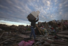 A man carries his belongings through debris after the suburb of Moore, Oklahoma was left devastated by a tornado, on May 21, 2013.REUTERS/Adrees Latif