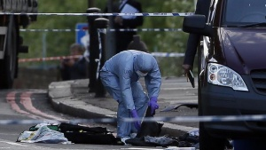 A police forensics officer investigates a crime scene where one man was killed in Woolwich, southeast London May 22, 2013. REUTERS/Stefan Wermuth