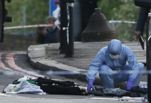 A police forensics officer investigates a crime scene where one man was killed in Woolwich, southeast London, May 22, 2013. REUTERS/Stefan Wermuth
