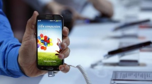 A man holds up Samsung Electronics Co's latest Galaxy S4 phone during its launch at the Radio City Music Hall in New York March 14, 2013. REUTERS/Adrees Latif/Files