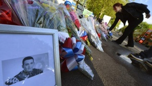 A picture of victim Drummer Lee Rigby, of the British Army's 2nd Battalion The Royal Regiment of Fusiliers is displayed with flowers left by mourners outside an army barracks near the scene of his killing in Woolwich, southeast London May 23, 2013. REUTERS/Toby Melville