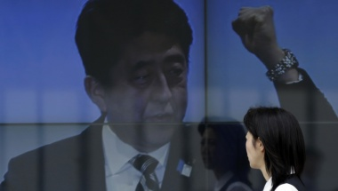 A woman walks past an electronic board displaying a photo of Japan's Prime Minister Shinzo Abe, a part of news of Abenomics, in Tokyo in this April 16, 2013 file photo. REUTERS/Toru Hanai/Files