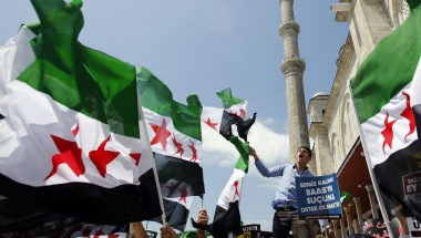 "Demonstrators shout Islamic slogans as they wave Syrian opposition flags during a protest against Syria's President Bashar al-Assad at the courtyard of Fatih mosque in Istanbul May 24, 2013. The sign reads, ""Being silent means to be take part in the crime of Baath.""     REUTERS/Murad Sezer"