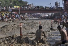 A Hindu devotee tries to take a holy dip in the flooded waters of river Ganges in Haridwar June 18, 2013. REUTERS/Stringer