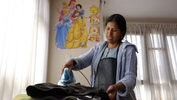 Rufina Condori, 34, who works as a maid, irons clothes in La Paz June 11, 2013. Condori works two jobs, which in total means she receives the monthly minimum wage equivalent to approximately $170.  REUTERS/David Mercado