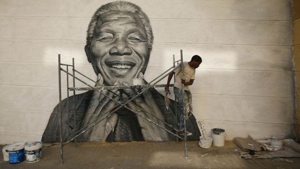 Nelson Tavares, 24, originally from Cape Verde, works on a graffiti of Nelson Mandela which he painted during festivities in his neighborhood in Lisbon June 20, 2013. Tavares works at a printing company where he charges the Portuguese minimum wage of 485 Euros. He studied at the school of arts, and is now preparing his first exhibition of paintings. Tavares lives with his parents. REUTERS/Rafael Marchante