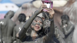 Tourists take pictures with a mobile phone after playing in the mud during the Boryeong Mud Festival at Daecheon beach in Boryeong, about 190 km (118 miles) southwest of Seoul, July 19, 2013. REUTERS/Lee Jae-Won/Files