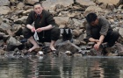 A North Korean soldier washes his socks as his comrade washes his hands at the banks of Yalu River, near the North Korean town of Sinuiju, opposite the Chinese border city of Dandong, April 8, 2013. REUTERS/Jacky Chen/Files