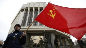 A man holds a Soviet Union flag as he attends a pro-Russian rally at the Crimean parliament building in Simferopol March 6, 2014. REUTERS/David Mdzinarishvili