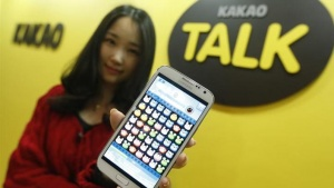 "An employee of mobile messager Kakao Talk displays the mobile game ""Anipang"" on a smartphone at the company in Seongnam, south of Seoul, March 26, 2013. REUTERS/Lee Jae-Won/Files"