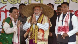 Narendra Modi, prime ministerial candidate for Bharatiya Janata Party (BJP) and Gujarat's chief minister, wearing a traditional hat presented to him by the party members greets his supporters during a rally ahead of the general election in Gogamukh in Lakhimpur district of Assam March 31, 2014. REUTERS/Utpal Baruah