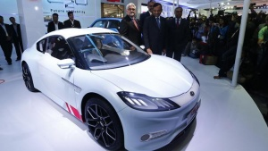 Pawan Goenka (C), president of Mahindra's automotive and farm equipment sectors, stands next to Mahindra's concept electric sports car 'Halo' after its unveiling during the Indian Auto Expo in Greater Noida, on the outskirts of New Delhi February 6, 2014.  REUTERS/Adnan Abidi
