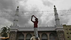 An electrician fixes lights on a mosque against the backdrop of monsoon clouds, during the holy month of Ramadan in Chennai August 5, 2013. REUTERS/Babu/Files