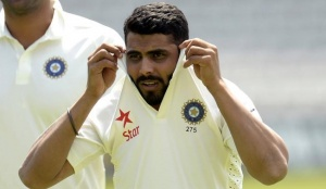 Ravindra Jadeja pulls up his shirt collar as he walks across the field during a training session at Lord's cricket ground in London July 16, 2014. REUTERS/Philip Brown