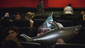 An audience member wearing a shark themed hat blows up an inflatable shark while attending a midnight screening of the U.S. cable television network Syfy film 'Sharknado' in New York, August 2, 2013. REUTERS/Lucas Jackson/Files