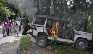 A demonstrator kicks a vehicle that was set on fire during a protest at Golaghat district in Assam August 20, 2014. REUTERS/Stringer/Files