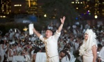 "Participants mug for a video camera as others dine al fresco at the 4th annual ""Diner en Blanc"" in the Manhattan borough of New York August 25, 2014. REUTERS/Carlo Allegri"