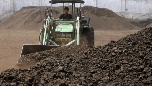 A worker uses a loader to assemble the coal at a yard in Ahmedabad March 22, 2012. REUTERS/Amit Dave/Files