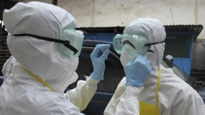 Health workers wearing protective clothing prepare themselves before to carrying an abandoned dead body presenting with Ebola symptoms at Duwala market in Monrovia August 17, 2014. REUTERS/2Tango/Files