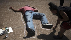An activist, demanding justice for the shooting death of teen Michael Brown, outlines a man lying on the pavement in front of City Hall in downtown St. Louis, Missouri, August 26, 2014. REUTERS/Adrees Latif