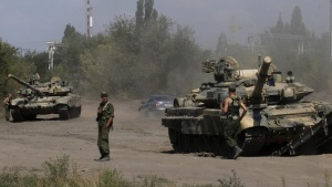 Russian soldiers are pictured next to tanks in Kamensk-Shakhtinsky, Rostov region, near the border with Ukraine, August 23, 2014. REUTERS/Alexander Demianchuk