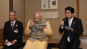 India's Prime Minister Narendra Modi (C) and Japan's Prime Minister Shinzo Abe (R) enjoy tea cakes during a tea ceremony at the Omotesenke tea hut, one of the main schools for Japanese tea ceremony, in Tokyo September 1, 2014. REUTERS/Yuya Shino