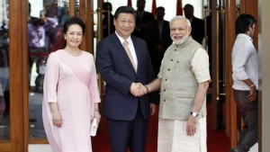 India's Prime Minister Narendra Modi (R) and China's President Xi Jinping (C) shake hands as Xi's wife Peng Liyuan looks on before their meeting in Ahmedabad September 17, 2014. REUTERS/Amit Dave