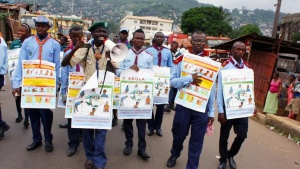 Members of a UNICEF-supported social mobilization team walk on a street, carrying posters with information on the symptoms of Ebola and best practices to help prevent its spread, in Freetown, Sierra Leone, in this handout photo courtesy of UNICEF taken in August 2014. REUTERS/Issa Davies/UNICEF/Handout via Reuters