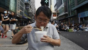 A protester eats noodles in the middle of a main road occupied by protesters, at Mongkok shopping district in Hong Kong September 30, 2014. REUTERS/Liau Chung-ren