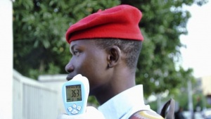 A school official takes a Goverment Secondary School Garki pupil's temperature using an infrared digital laser thermometer in front of the school premises, as school resumes in Abuja September 22, 2014. REUTERS/Stringer/Files