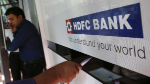 A customer walks out of a HDFC Bank branch as another deposits a cheque at a counter in Mumbai November 17, 2012. REUTERS/Vivek Prakash/Files
