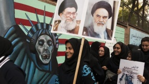 Students take part in a demonstration as one of them holds pictures of Iran's Supreme Leader Ayatollah Ali Khamenei (L) and founder of the Islamic Republic Ayatollah Ruhollah Khomeini outside the former U.S. embassy in Tehran November 4, 2010. REUTERS/Raheb Homavandi/Files