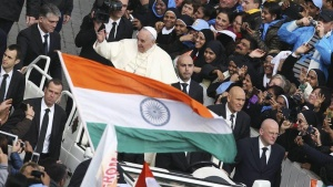 Pope Francis gestures as an Indian national flag is waved during a canonisation ceremony to make saints out of six men and women, in Saint Peter's square at the Vatican November 23, 2014. REUTERS/Alessandro Bianchi