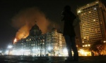 A reporter talks on her phone as smoke is seen coming from Taj Hotel in Mumbai November 27, 2008. REUTERS/Arko Datta/Files