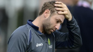 Australia's Phillip Hughes touches his head during a training session before Thursday's third Ashes cricket test match against England at Old Trafford cricket ground in Manchester July 30, 2013. REUTERS/Philip Brown/Files