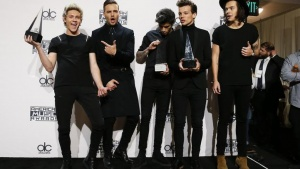 "One Direction poses backstage with their awards for Favorite Rock/Pop Band/Duo/Group, Artist of the Year and Favorite Rock/Pop Album for ""Midnight Memories"" during the 42nd American Music Awards in Los Angeles, California November 23, 2014.  REUTERS/Danny Moloshok"