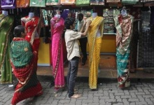 A worker arranges sarees, a traditional cloth used for women's clothing outside a shop in Mumbai September 19, 2012. India's organised retail market could attract up to $16 billion in foreign direct investment (FDI) over the next three years, much of that in the farm-to-store supply chain network, according to estimates by Boston Consulting Group. REUTERS/Danish Siddiqui (INDIA - Tags: BUSINESS) - RTR385FX