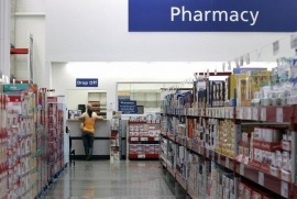 A customer leans against the pharmacy counter at a Sam's Club store in Bentonville, Arkansas May 31, 2007. REUTERS/Jessica Rinaldi